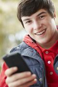 Teenage Boy Texting On Smartphone Wearing Winter Clothes Stock Photos