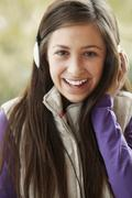 Teenage Girl Wearing Headphones And Listening To Music Wearing Winter Clothes - stock photo