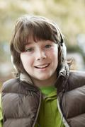 Boy Wearing Headphones And Listening To Music Wearing Winter Clothes - stock photo