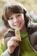 Boy Eating Healthy Snack Bar Wearing Winter Clothes Stock Photos