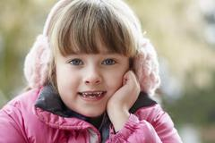 Outdoor Portrait Of Young Girl Wearing Winter Clothes And Earmuffs - stock photo