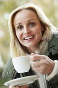 Woman In Outdoor Caf̩ With Hot Drink  Wearing Winter Clothes - stock photo