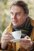 Man In Outdoor Caf̩ With Hot Drink  Wearing Winter Clothes Stock Photos