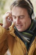 Man Wearing Headphones And Listening To Music Wearing Winter Clothes - stock photo