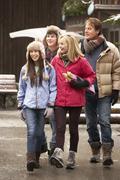 Teenage Family Walking Along Snowy Town Street In Ski Resort Stock Photos