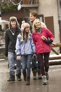 Teenage Family Walking Along Snowy Town Street In Ski Resort - stock photo