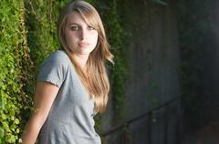 Teenage girl stands near vines in the shade facing right Stock Photos