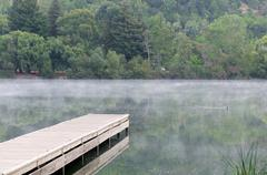 Stock Photo of Wooden pier on a calm lake with fog