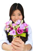 woman smiling and showing flowers - stock photo