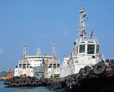 a row of tugboats in the harbor - stock photo