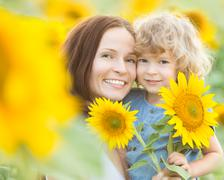 Happy family with beautiful sunflowers Stock Photos