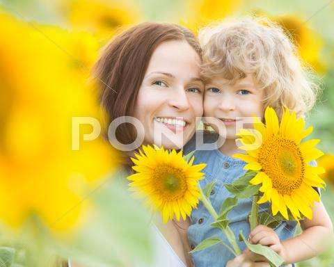 Stock photo of happy family with beautiful sunflowers