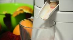 Glass filling up with fresh healty orange and beetroot juice from juicer Stock Footage