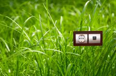 electric outlet in grass.ecology clean electricity concept. - stock photo