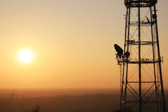 communication tower at sunset with cityscape - stock photo