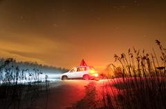 winter night with snow and car with headlights on. - stock photo