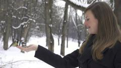 SLOW MOTION: Bird lands on girl's hand and eats seeds Stock Footage