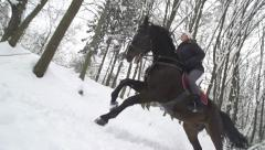 SLOW MOTION: Woman and her horse cantering in fresh snow Stock Footage