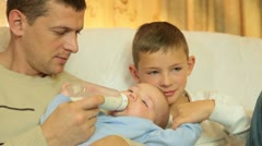 Father feeding his baby boy at home - stock footage