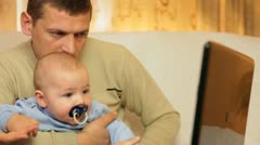 Father and baby using laptop Stock Footage