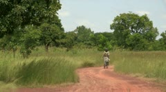 Burkina Faso: Woman on Bicycle on African Road Stock Footage
