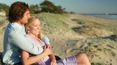 Young Couple Sitting on Beach Medium View Stock Footage