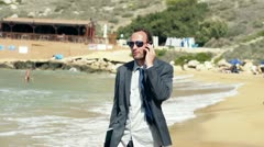 Businessman on the beach talking on cellphone, slow motion 240fps Stock Footage