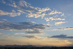 blue sky, clouds and mountain range - stock photo