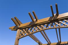 wooden pergola against a blue sky - stock photo
