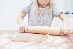 Young girl making gingerbread Stock Photos