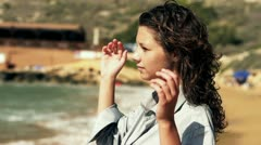 Young woman dissolves hair on the beach, slow motion shot at 120fps Stock Footage