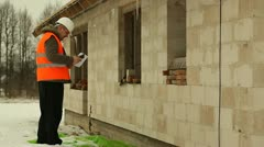 Construction manager with cell phone  near new building - stock footage