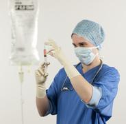 surgical nurse controls syringe - stock photo