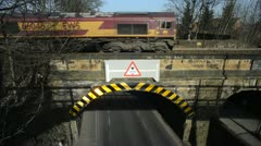Freight train crossing rail bridge over road at Woodlesford leeds united kingdom Stock Footage