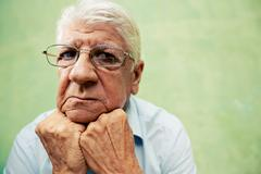 Portrait of serious old man looking at camera with hands on chin Stock Photos