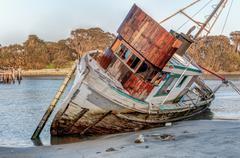 Shipwreck Awash on Beach Stock Photos