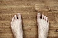Stock Photo of man feet on parquet