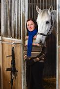 woman and white horse inside a stall, vertical format - stock photo