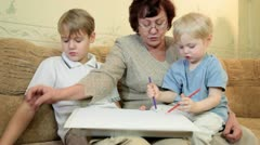 Granny with kids painting at home Stock Footage