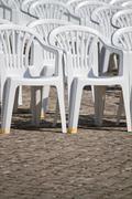 aligned white plastic chairs - stock photo