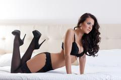 Young attractive brunette in black lingerie Stock Photos