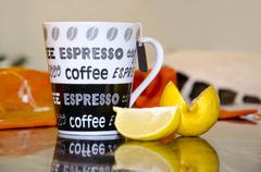 cup of coffee with lemon slice reflection and blur background - stock photo