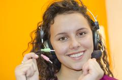 Beautiful young teenage girl with black curly hair happy listening music on h Stock Photos