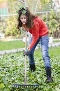 Young girl with a rake tool cleaning garden green leafs Stock Photos