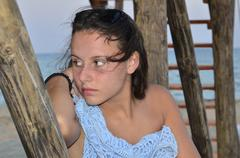Portrait of young beautiful girl with inocent look on sea wooden house posts Stock Photos