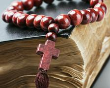 Wooden rosary on the bible are Stock Photos