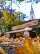 Background bench autumnal leaves church in Stock Photos
