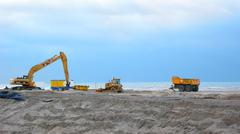 Beach dike for amplifying coast see bulldozer Stock Photos