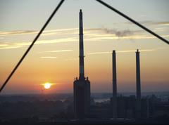 chimneys factory fumes sunset austria horizontal - stock photo