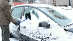 man removing cleaning snow car window brush winter parking house - stock footage